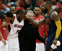 Cleveland Cavaliers forward LeBron James, right, speaks with an injured Atlanta Hawks forward DeMarre Carroll (5) as Carroll is helped of the court during the second half in Game 1 of the Eastern Conference finals of the NBA basketball playoffs, Wednesday, May 20, 2015, in Atlanta. (AP Photo/John Bazemore)