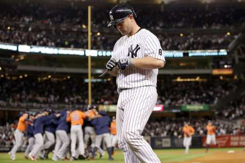 Brian McCann tears off the batting gloves as Houston celebrates a 3 - 0 victory over the NY Yankees on October 6th/Photo Credit: Adam Hunger USA Today Sports